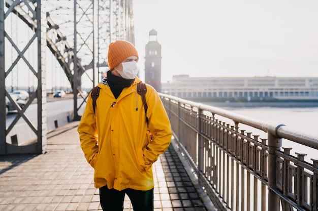 Młody człowiek ubrany w medyczną maskę chirurgiczną, pomarańczową czapkę i żółtą wiatrówkę z niepokojem, myślący o koronawirdzie pandemicznym, stojący na moście w pustym mieście. koncepcja wirusa covid-19.