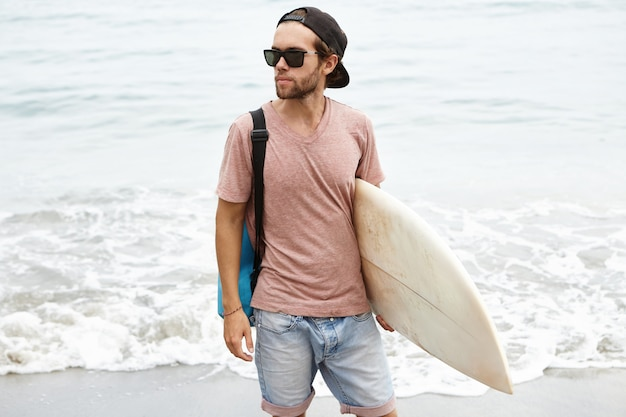 Młody człowiek ubrany w modne okulary przeciwsłoneczne i snapback, trzymając w ręku deskę surfingową