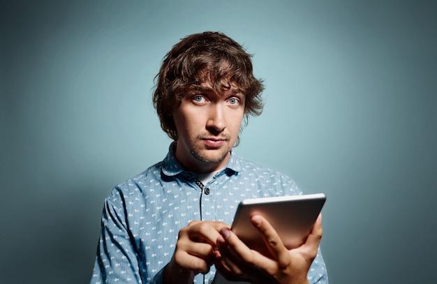 Młody człowiek ubrany w niebieską koszulę i trzymając tablet