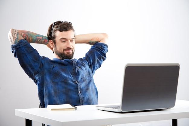 Młody człowiek ubrany w niebieską koszulę siedzi z laptopem i pracy, niezależna koncepcja, udany projekt.
