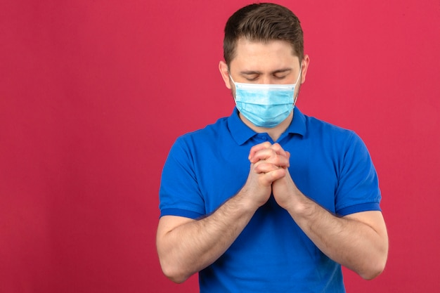 Młody człowiek ubrany w niebieską koszulkę polo w medycznej masce ochronnej, stojący z zamkniętymi oczami, trzymając ręce razem, jak modląc się nad izolowaną różową ścianą