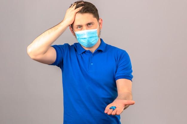 Młody człowiek ubrany w niebieską koszulkę polo w medycznej masce ochronnej, wyglądający źle i chory, stojąc z ręką na głowie cierpiącej na ból głowy, trzymając skórki w otwartej dłoni nad izolowaną pomarańczową ścianą