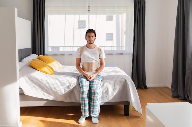 Młody człowiek ubrany w pasek wsparcia z tyłu. orteza lędźwiowa, wsparcie pleców w przypadku urazu pleców lub napięcia mięśni pleców