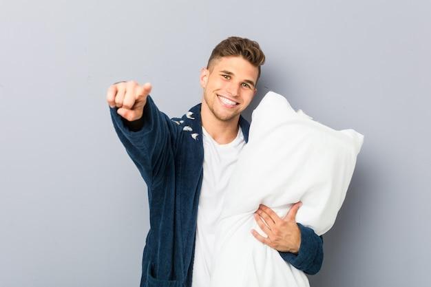 Młody człowiek ubrany w pijama trzyma poduszkę wesoły uśmiech wskazuje na przód