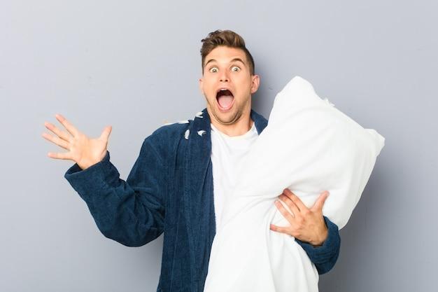 Młody człowiek ubrany w pijama trzyma poduszkę z okazji zwycięstwa lub sukcesu