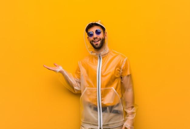 Młody człowiek ubrany w płaszcz przeciwdeszczowy, trzymając coś ręką