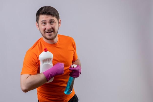 Młody człowiek ubrany w pomarańczowy t-shirt i gumowe rękawiczki, trzymając butelki ze środkami czyszczącymi, uśmiechając się radośnie