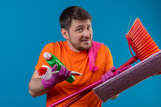 Młody człowiek ubrany w pomarańczowy t-shirt i gumowe rękawiczki, trzymając narzędzia do czyszczenia
