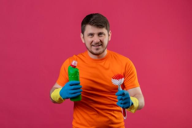 Młody człowiek ubrany w pomarańczowy t-shirt i gumowe rękawiczki, trzymając środki czystości i szczotka do szorowania