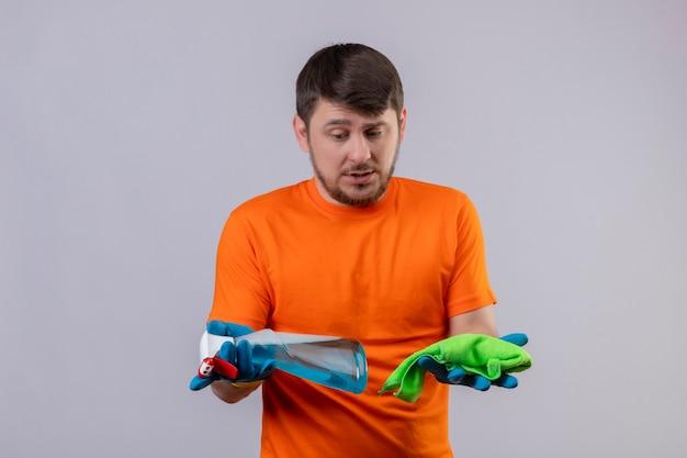 Młody człowiek ubrany w pomarańczowy t-shirt i rękawice gumowe, trzymając spray do czyszczenia i dywan, patrząc na nich
