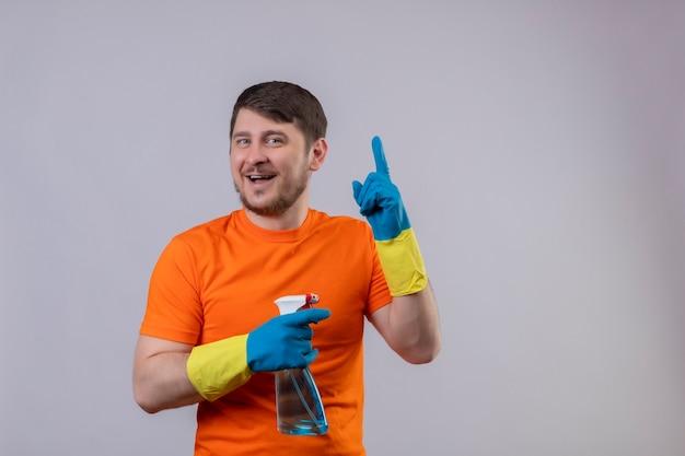 Młody człowiek ubrany w pomarańczowy t-shirt i rękawice gumowe, trzymając spray do czyszczenia, uśmiechając się radośnie