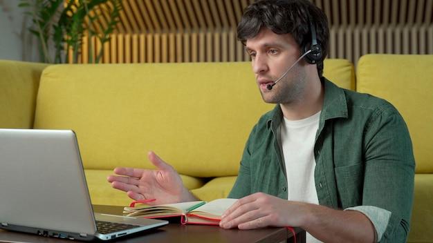 Młody człowiek ubrany w słuchawki siedzi na żółtej kanapie w domu i rozmawia przez łącze wideo na laptopie