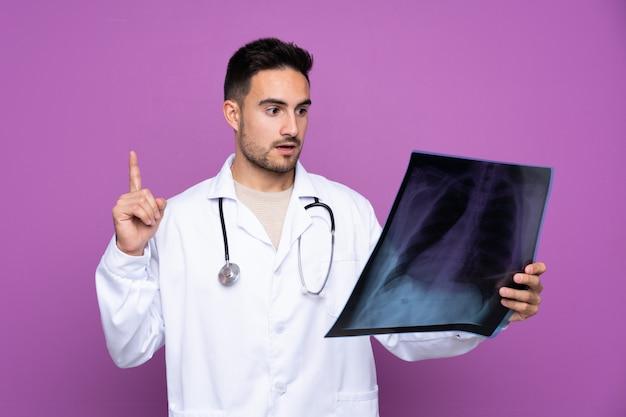 Młody człowiek ubrany w suknię lekarza i trzymając skan kości