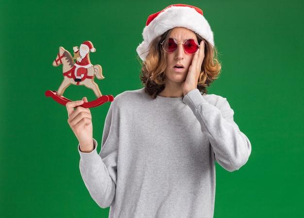 Młody człowiek ubrany w świąteczny santa hat i czerwone okulary trzyma aparat bożonarodzeniowy zabawki zdezorientowany i bardzo zaniepokojony patrząc na stojącego na zielonym tle
