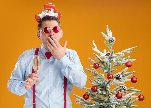 Młody człowiek ubrany w szelki muszka w obręczy z santa i czerwonymi okularami stojący obok choinki trzymając kieliszek szampana
