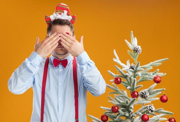 Młody człowiek ubrany w szelki muszka w obręczy z santa i czerwonymi okularami stojący obok choinki zasłaniającej twarz rękami nad pomarańczową ścianą