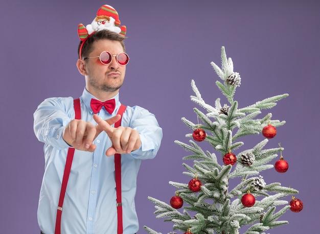 Młody człowiek ubrany w szelki muszka w obręczy z santa i czerwonymi okularami stojący obok choinki