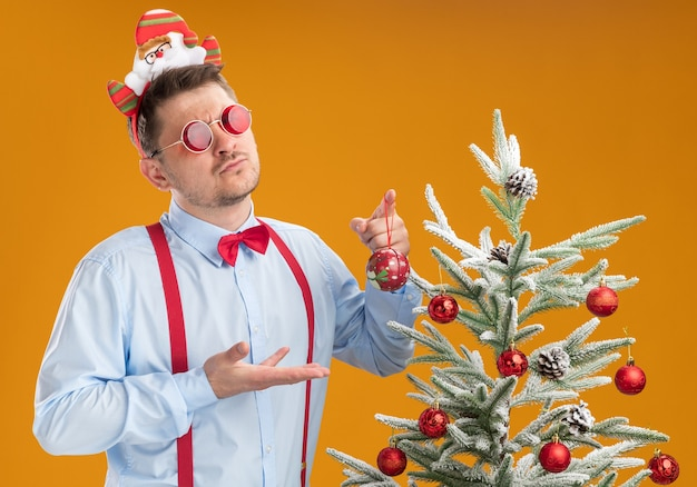 Młody człowiek ubrany w szelki muszka w santa hat i czerwone okulary stojąc obok choinki nad pomarańczową ścianą