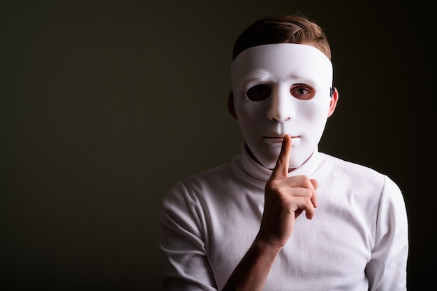 Młody człowiek ubrany w tajemniczą białą maskę