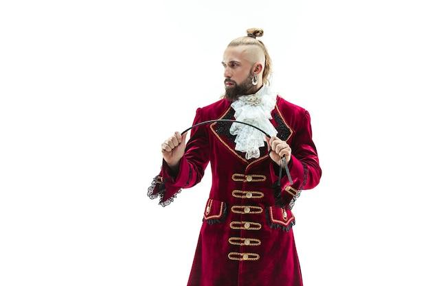 Młody człowiek ubrany w tradycyjny średniowieczny strój markiza pozuje w studio z biczem