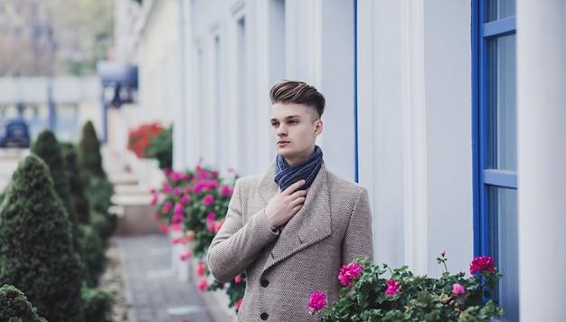 Młody człowiek ubrany w ubranie na ulicy. facet z nowoczesną fryzurą i płaszczem