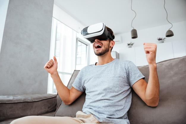 Młody człowiek ubrany w urządzenie wirtualnej rzeczywistości i robiąc gest zwycięzcy siedząc na kanapie.