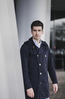 Młody człowiek ubrany w wiosenne ubrania na ulicy. młody facet z nowoczesną fryzurą
