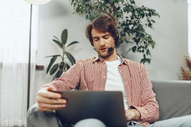 Młody człowiek ubrany w zestaw słuchawkowy prowadzi rozmowę wideo przez laptopa