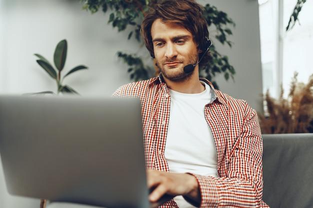 Młody człowiek ubrany w zestaw słuchawkowy robi połączenie wideo przez laptopa