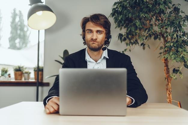 Młody człowiek ubrany w zestaw słuchawkowy robi rozmowę wideo przez laptopa