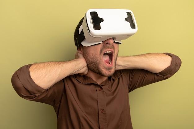Młody człowiek ubrany w zestaw słuchawkowy vr, trzymając ręce za szyją, patrząc na bok krzycząc na białym tle na oliwkowej ścianie