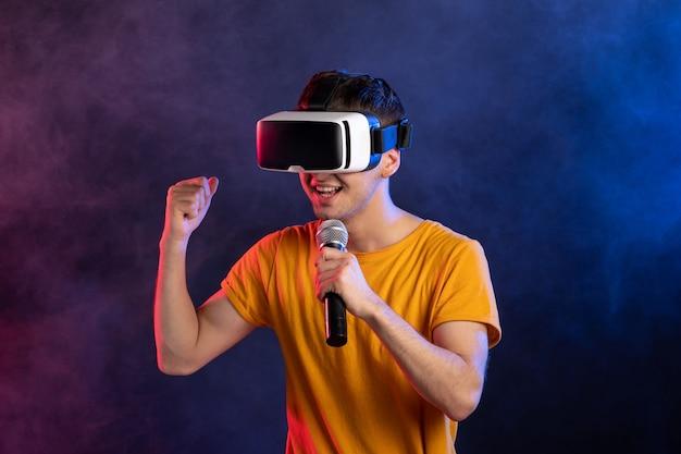 Młody człowiek ubrany w zestaw słuchawkowy wirtualnej rzeczywistości i trzymając mikrofon ciemnoniebieską powierzchnię