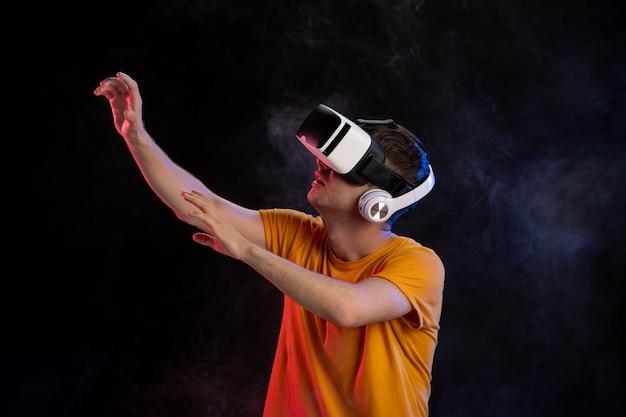 Młody człowiek ubrany w zestaw słuchawkowy wirtualnej rzeczywistości na ciemnej powierzchni