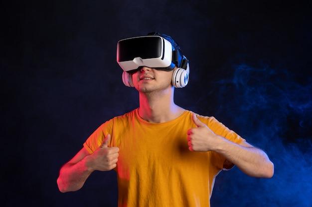 Młody człowiek ubrany w zestaw słuchawkowy wirtualnej rzeczywistości na ciemnoniebieskiej powierzchni