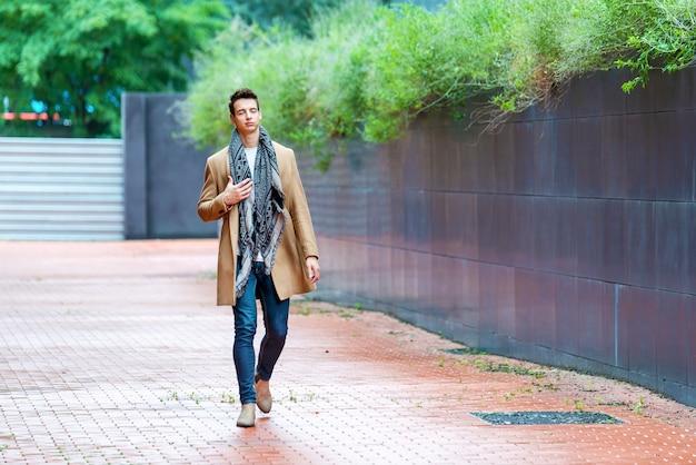Młody człowiek ubrany w zimowe ubrania na ulicy. młody chłopak z nowoczesną fryzurę w mieście