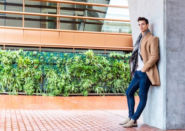 Młody człowiek ubrany w zimowe ubrania na ulicy.