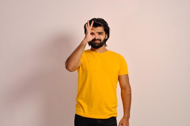 Młody człowiek ubrany w żółtą koszulkę i robiący ok gest ręką uśmiechniętą oczy patrzącą przez palce