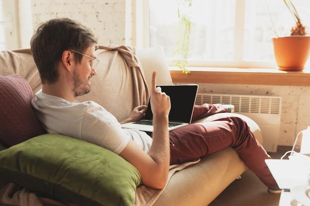 Młody człowiek uczący się w domu podczas kursów internetowych dla dziennikarzy, krytyków, pisarzy. zdobywanie zawodu w izolacji, kwarantanna przeciwko rozprzestrzenianiu się koronawirusa. korzystanie z laptopa, smartfona, słuchawek.