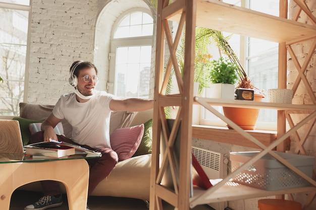 Młody człowiek uczący się w domu podczas kursów online dla robotnika, dziennikarza, programisty.