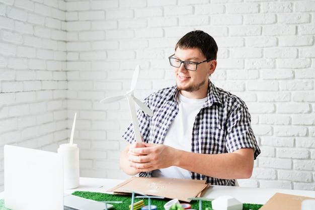 Młody człowiek uczy online co manekin energii odnawialnej
