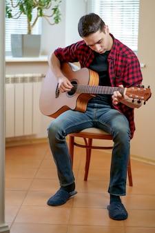 Młody człowiek uczy się gry na gitarze za pomocą internetu, laptopa, lekcji online