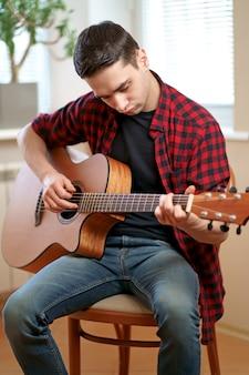 Młody człowiek uczy się gry na gitarze za pomocą laptopa internetowego, lekcji online hobby i koncepcji rekreacji