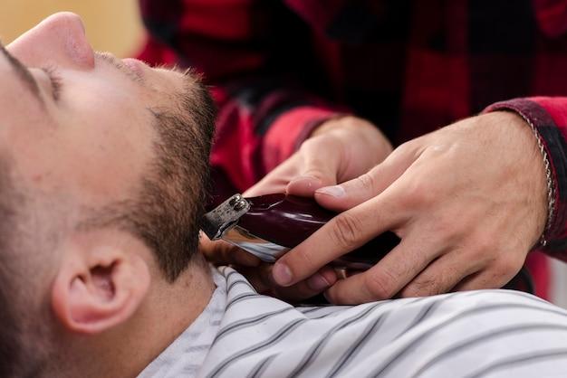 Młody człowiek układa brodę maszyną do golenia