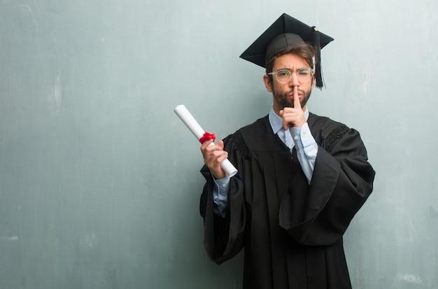Młody człowiek ukończył studia na ścianie grunge z przestrzenią do kopiowania, utrzymując tajemnicę lub prosząc o ciszę