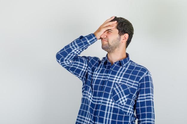 Młody człowiek umieszczając rękę na głowie w kraciastej koszuli i patrząc z żalem