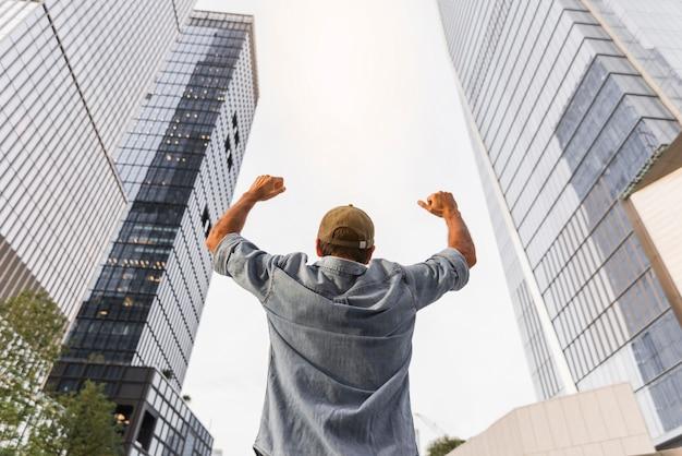 Młody człowiek unosi pięści w powietrzu