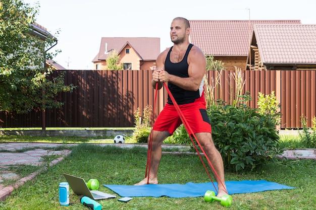 Młody człowiek uprawia sport w domu na podwórku w letni dzień. młody sportowiec o blond włosach robi przysiad z gumą sportową na macie, jest laptop, piłka, hantle.