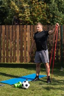 Młody człowiek uprawia sport w domu na podwórku w letni dzień. młody sportowiec o blond włosach ściska dłoń sportową gumą na macie, jest piłka, hantle.