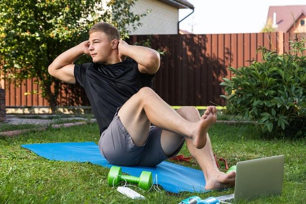 Młody człowiek uprawia sport w domu na podwórku w letni dzień, trenując online. sportowiec robi prasę na macie w ogrodzie