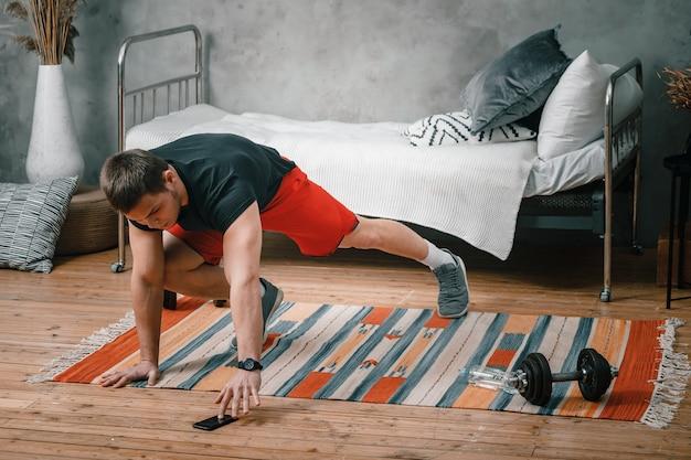 Młody człowiek uprawia sport w domu, trening online przez telefon. sportowiec rzuca się, ogląda film i portale społecznościowe w sypialni, w tle łóżko, wazon, dywan.